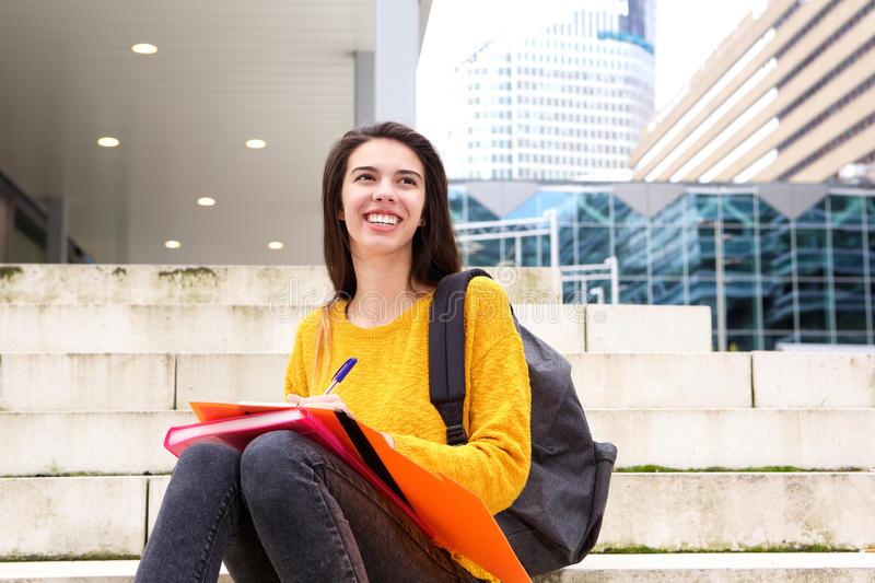 Smiling young woman writing in notebook. Portrait of smiling young woman writing in notebook royalty free stock photography