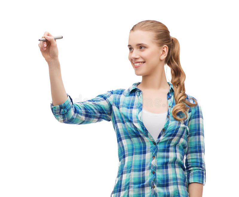 Smiling young woman writing on virtual screen. Happiness and people concept - smiling young woman writing or drawing something on virtual screen stock image