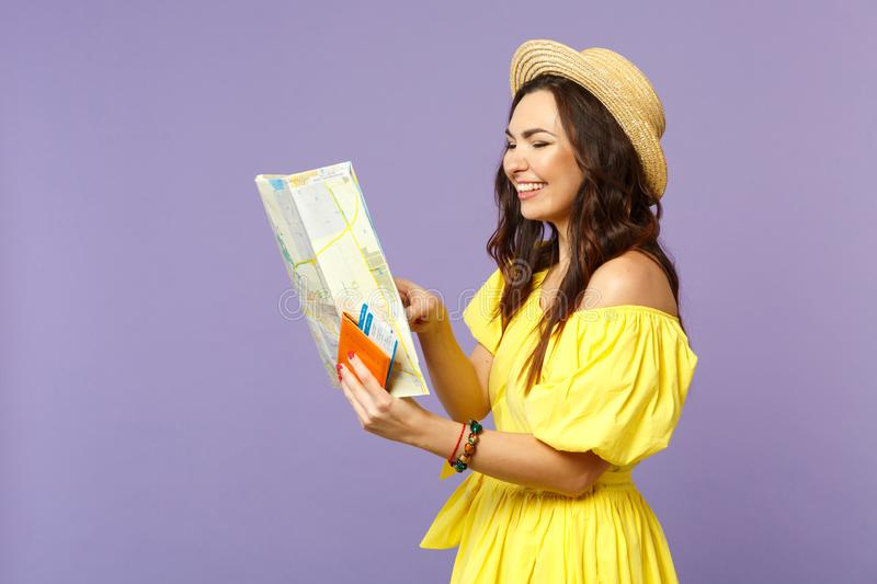 Smiling young woman in yellow dress, summer hat hold city map, passport boarding pass ticket isolated on pastel violet royalty free stock photography