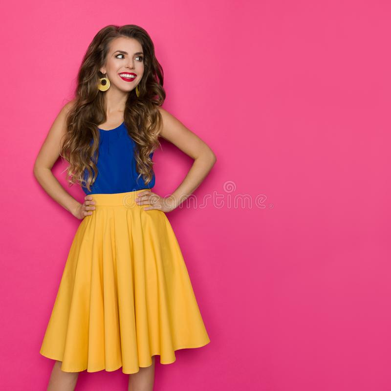 Smiling Young Woman In Yellow Skirt And Blue Top Is Looking Away royalty free stock photos