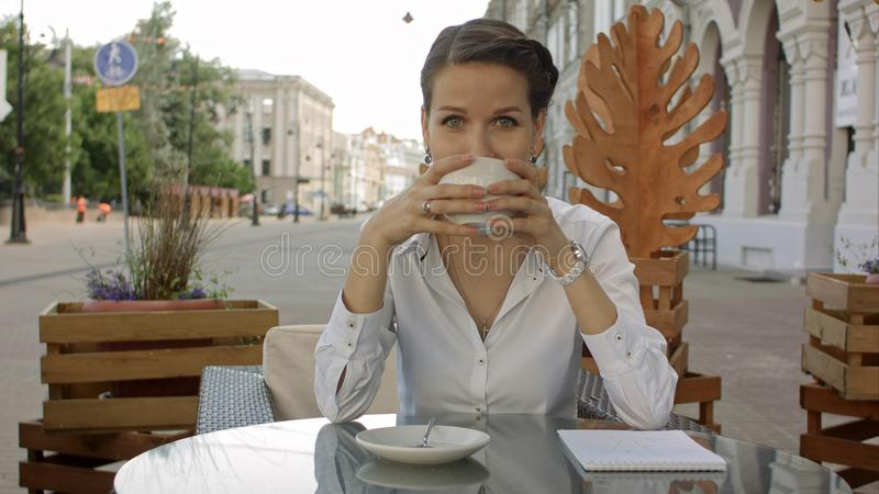 Smiling young women drinking coffee or tea and gossiping at outdoor cafe royalty free stock photography