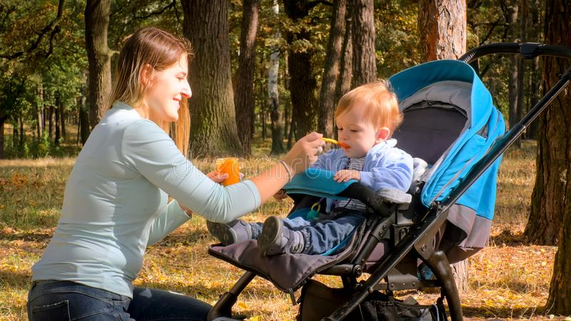 Portrait of smiling young woman feeding her baby sitting in pram with porridge stock photos