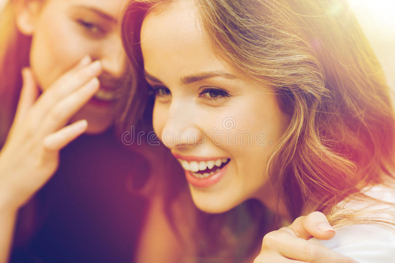Smiling young women gossiping and whispering. People, communication and friendship concept - smiling young women gossiping and whispering secrets royalty free stock photos