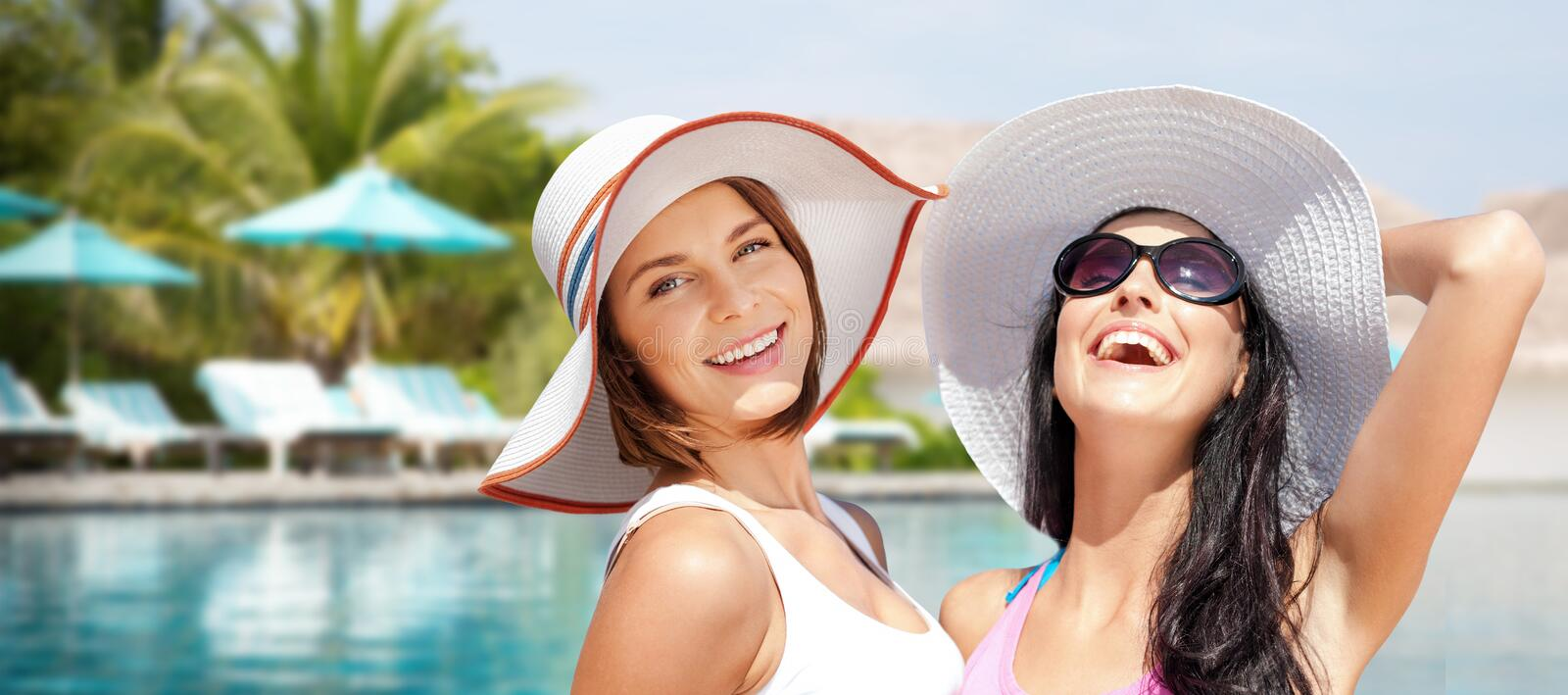 Smiling young women in hats on beach royalty free stock image
