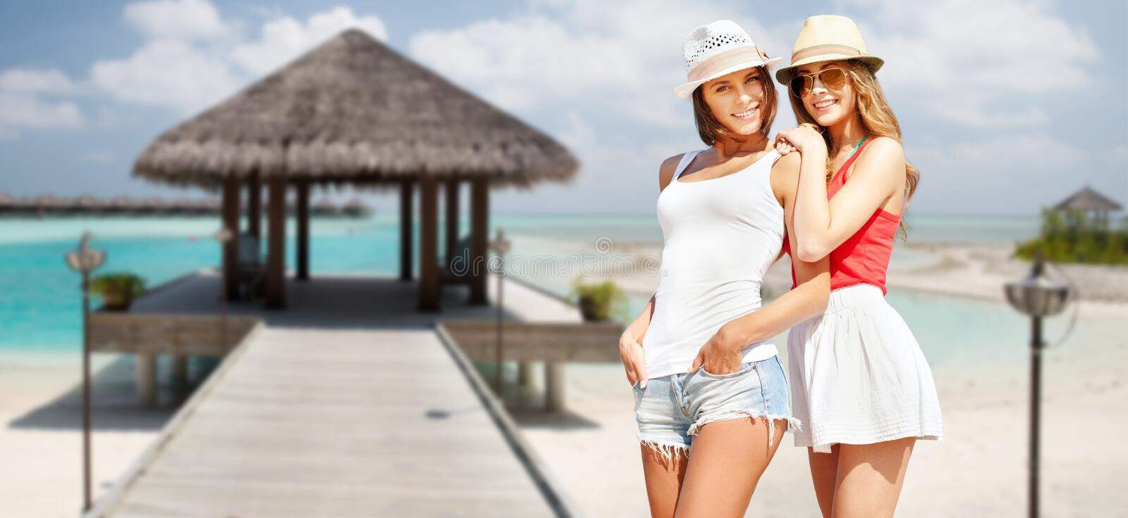 Smiling young women in hats on beach stock image