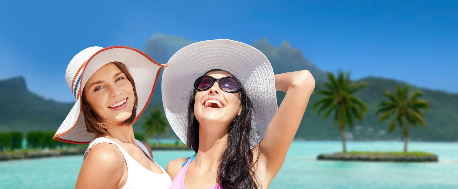 Smiling young women in hats on bora bora beach stock images