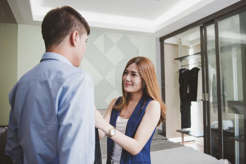 Smiling young woman helping her husband with necktie. stock photo