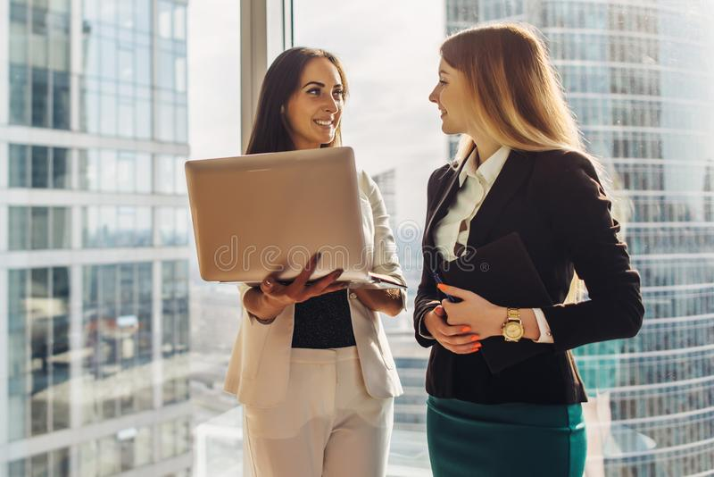 Smiling young women with laptop standing and talking in office stock photo