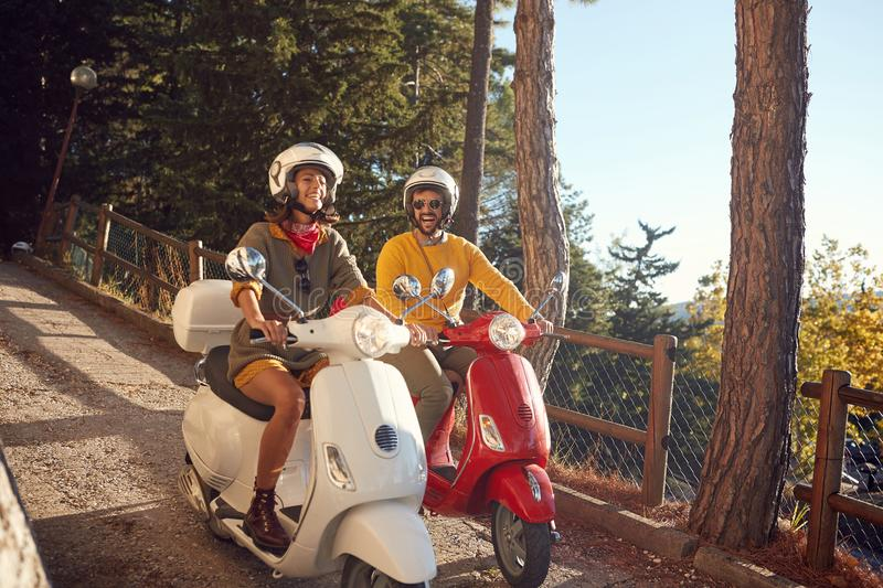 Smiling woman and men riding a scooter and looking at Italy on vacation. Smiling young women and men riding a scooter and looking at Italy on vacation royalty free stock images