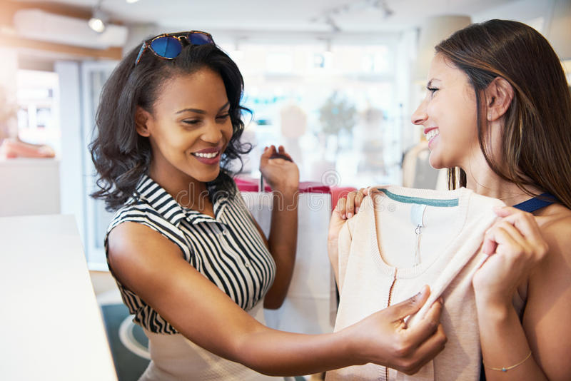 Smiling young women shopping for summer clothes stock photos