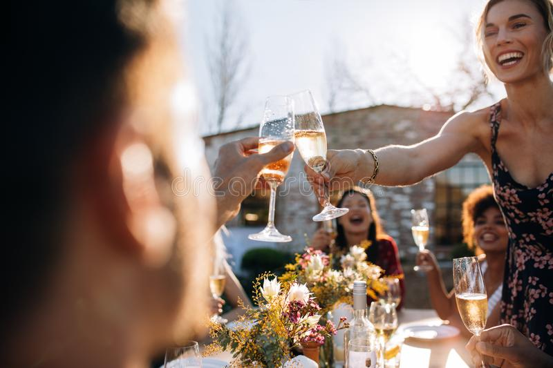 Woman toasting champagne with friend at party. Smiling young women toasting champagne with friend during an outdoor party. Young people enjoying at party with royalty free stock photo