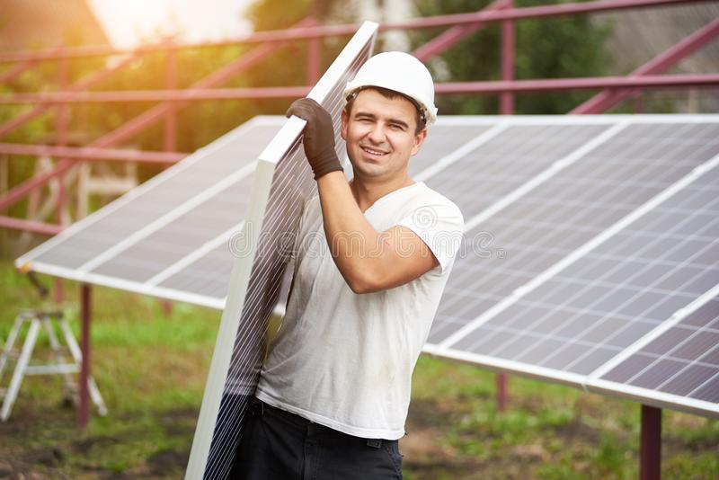 Installation of stand-alone exterior photo voltaic panels system. Renewable green energy generation. Smiling young worker in protective helmet carrying big royalty free stock photography