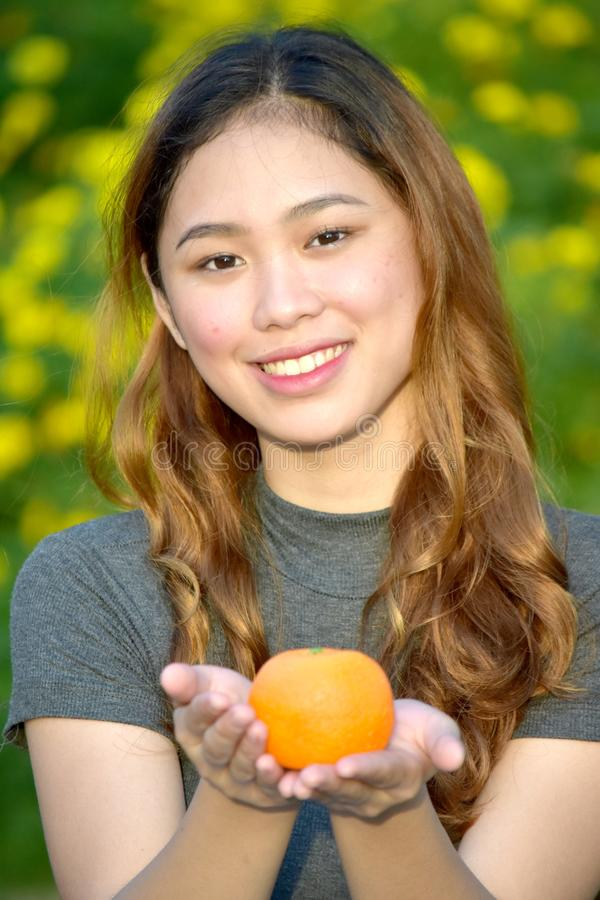 Smiling Youthful Asian Female With An Orange. An attractive and asian person stock photos