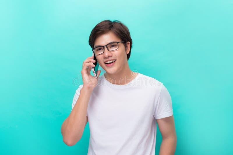 smilling和使用他的智能手机的年轻亚洲英俊的商人 愉快和使用智能手机的亚裔商人画象  图库摄影