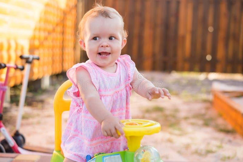 Smilling女婴骑马玩具汽车在庭院里 库存照片
