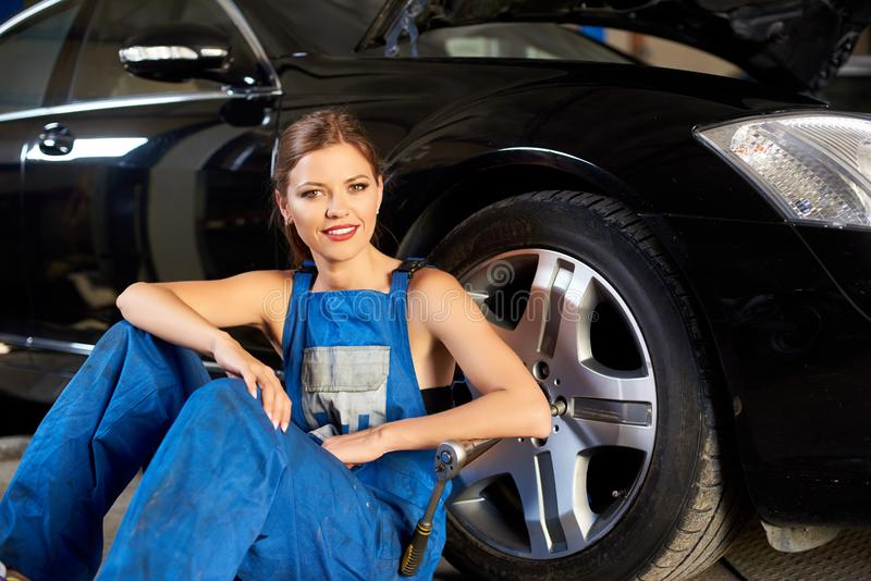 Smilling技工女孩在黑汽车附近轮子坐 免版税图库摄影