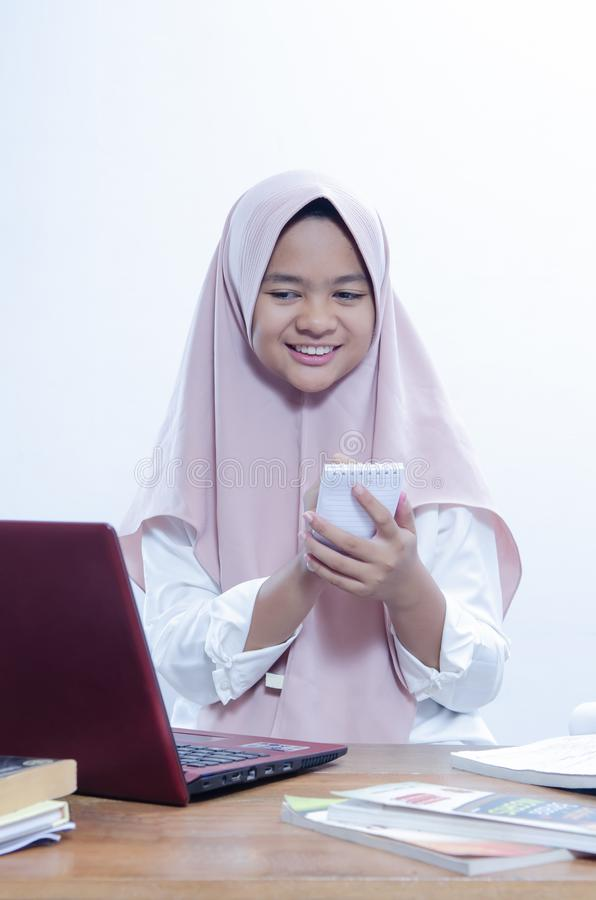 smilling确信的年轻女人的画象,当工作在她的有她的红色膝上型计算机的办公室和写在她的笔记本时 库存照片