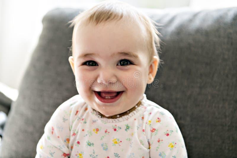 Smilling младенец на сером кресле стоковое изображение