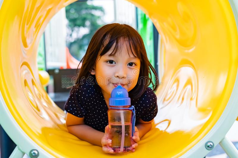 Smilling Asian Girl Drinking Water in the Playground. Smiling Asian Girl Drinking Water in the Playground stock images