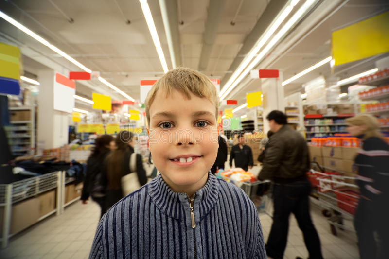 Smilling boy stand in centre in supermarket