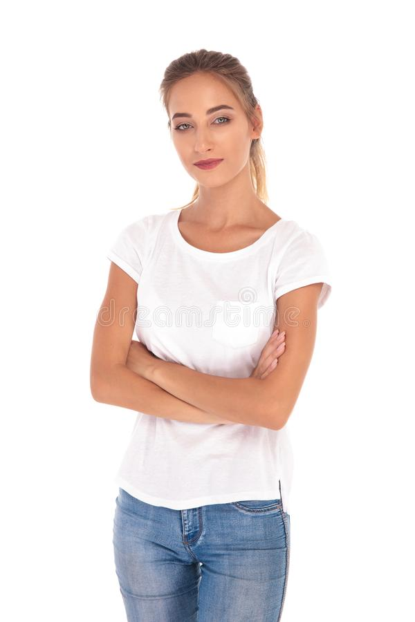 Smilling and confident young casual woman standing with arms fol royalty free stock image