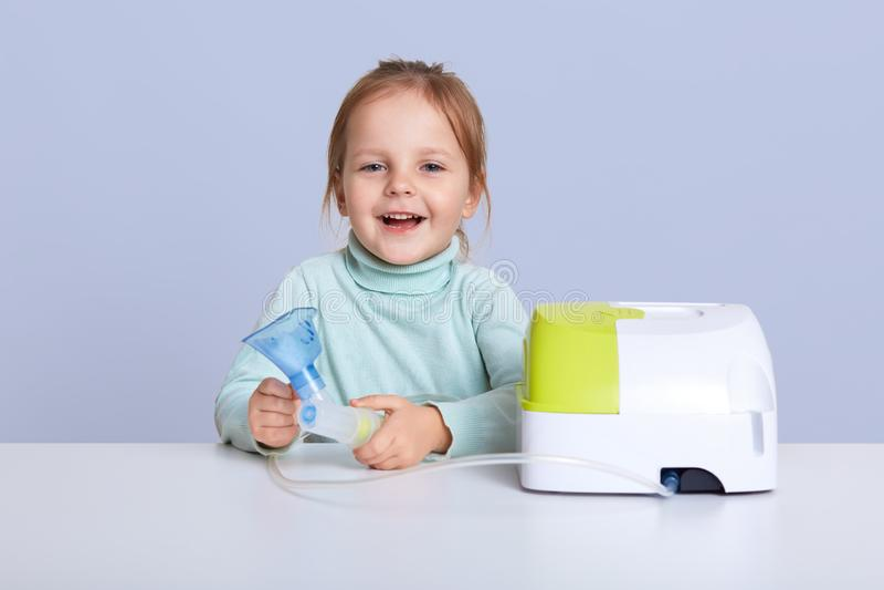 Smilling di seduta della bambina graziosa allo scrittorio bianco, tenente l'inalatore di asma, ha espressione facciale felice, ha fotografie stock