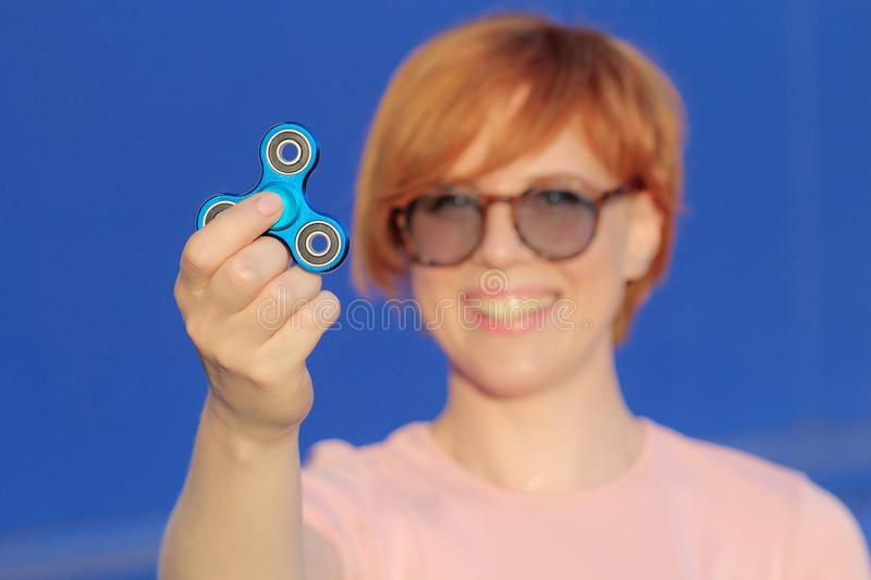 Smilling girl in pink t-shirt is playing blue metal spinner in hands on the street, woman playing with a popular fidget spinner to stock images