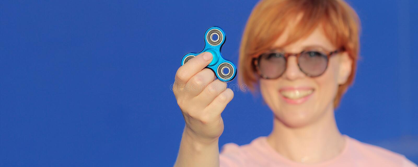 Smilling girl in pink t-shirt is playing blue metal spinner in hands on the street, woman playing with a popular fidget spinner to stock image