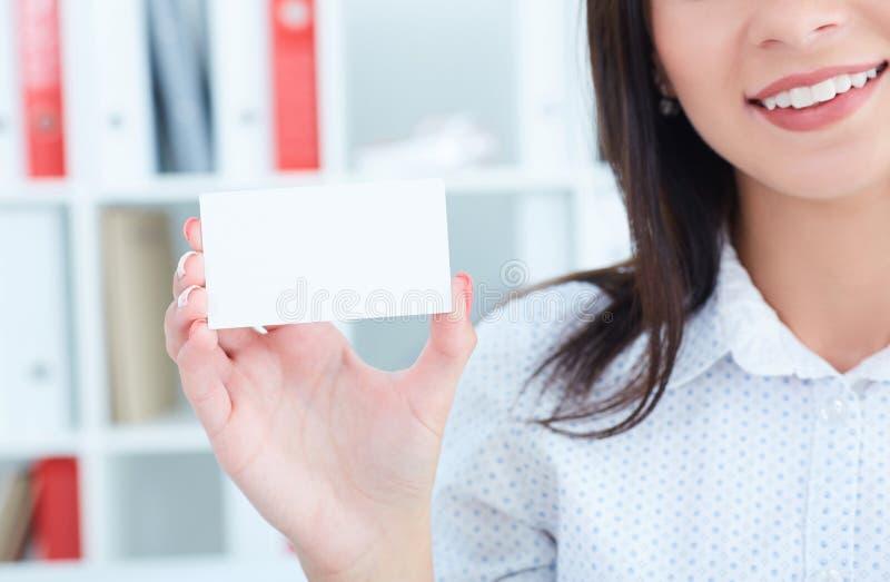 Smilling kvinna som visar det tomma tomma tecknet för pappers- kort med kopieringsutrymme för text Annonseringbegrepp arkivfoto