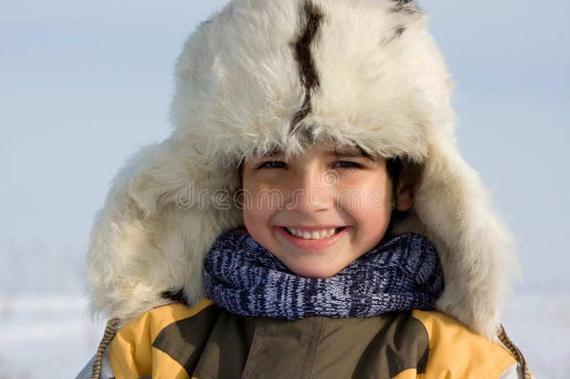 Smilling little boy in the fur-cap. Cute little boy winter portrait in the fur-cap stock image
