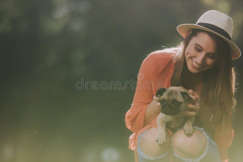 Smilling rymmer den gulliga kvinnan hennes hund arkivfoto