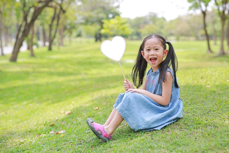Smilling weinig Aziatisch leeg het hartetiket die van de meisjesholding op groen gras bij de zomertuin liggen royalty-vrije stock fotografie