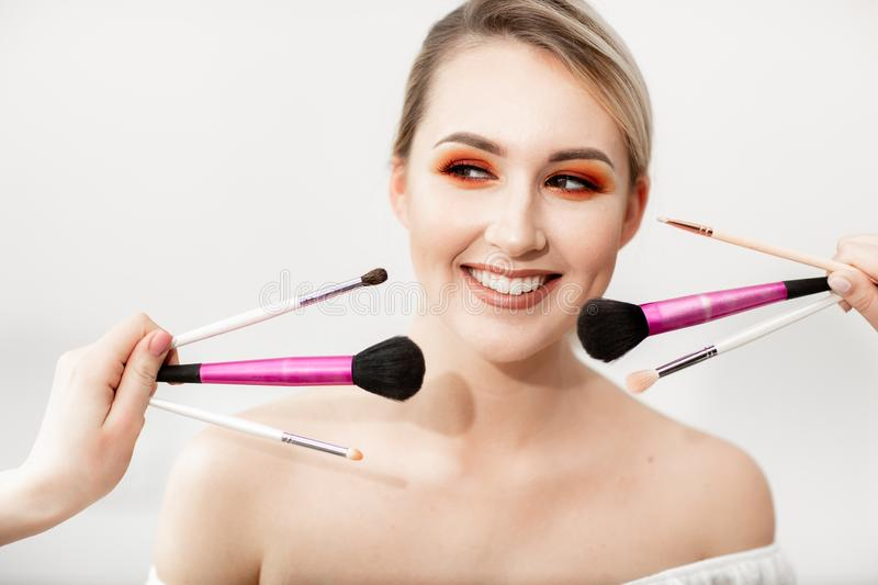 Young blond woman with orange-brown bright makeup. In front of her face the hands holding various makeup brushes royalty free stock photography