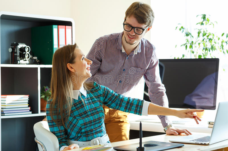 Smillingl young woman and man working from home. Smillingl young women and men working from home - modern business concept stock image