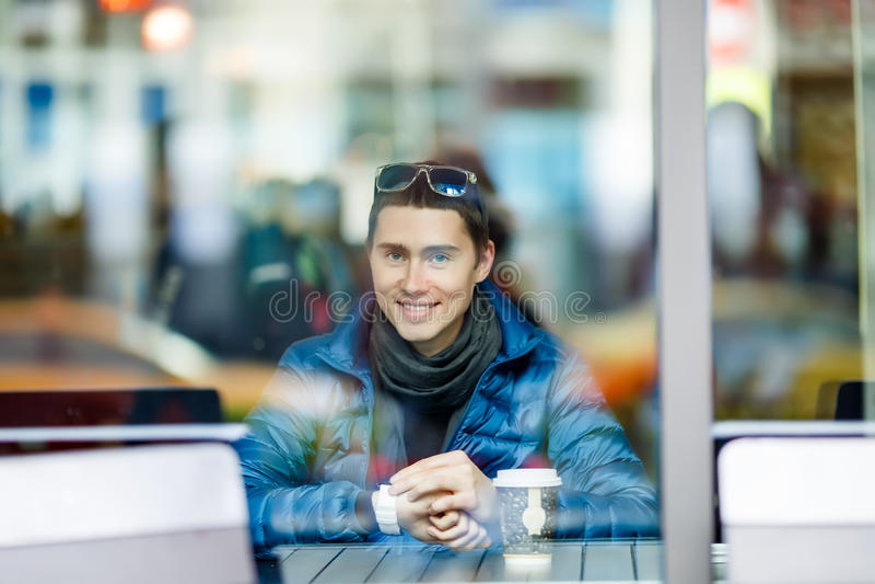 Smillingsmens met een kop van koffie in een koffie royalty-vrije stock afbeelding