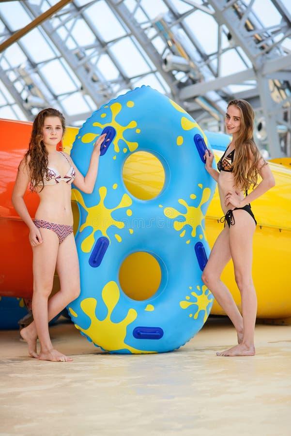 Smilng kvinnor i bikinin som står den near vattenglidbanan i aquaen, parkerar royaltyfri fotografi
