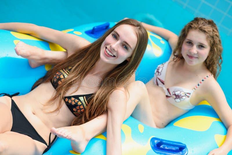 Smilng kvinnor i bikiniridning på vattenglidbanan i aquaen parkerar arkivfoton