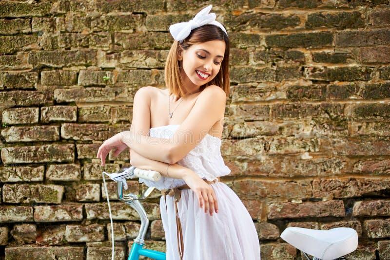 Smilong het mooie meisje stellen dichtbij een bakstenen muur met een blauwe fiets royalty-vrije stock afbeeldingen
