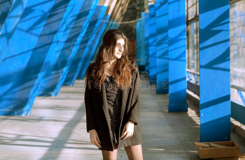 Smily brunettflickaanseende mellan blåa väggar av grungestadsområde Ung kvinna som ser bra i stads- inre arkivfoto