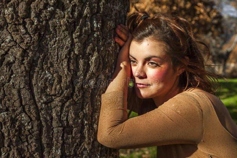 Smily młodej kobiety pozycja w drzewie target226_0_ patrzeć Zmierzch jesień zdjęcia royalty free