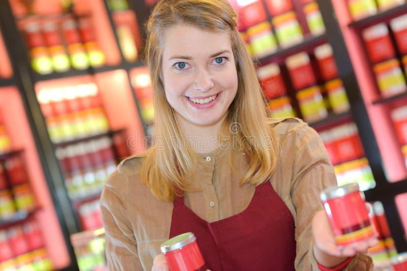 Smily ung kvinna som väljer sälja te royaltyfria foton