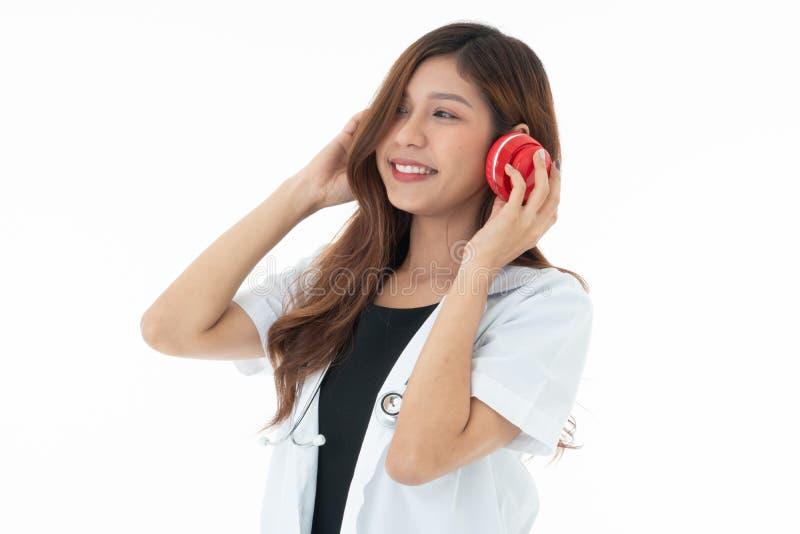 Smily vrouw arts dragen rode hoofdtelefoons met een sthethoscope op haar hals royalty-vrije stock foto's