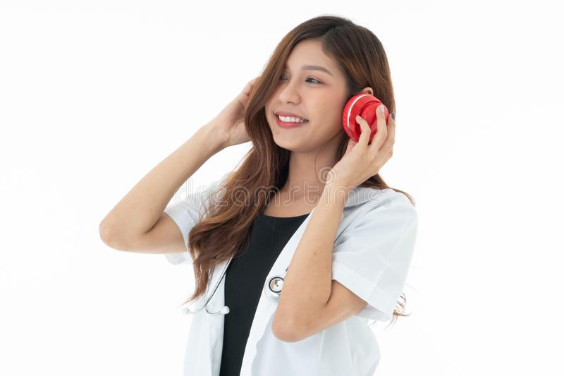 A smily woman doctor wearing a red headphones with a sthethoscope on her neck royalty free stock photos