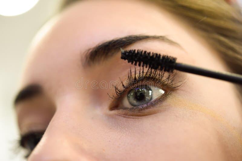 Smink applicera mascara Långa ögonfrans och blåa ögon royaltyfri fotografi