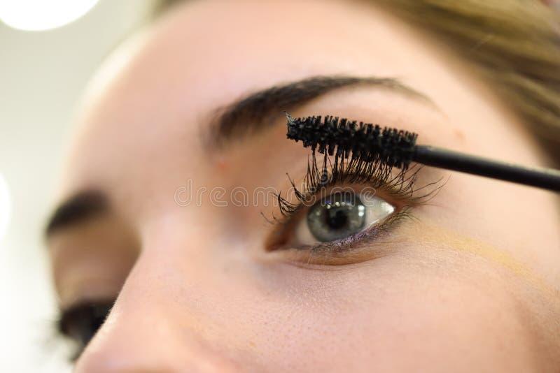 Smink applicera mascara Långa ögonfrans och blåa ögon royaltyfria bilder
