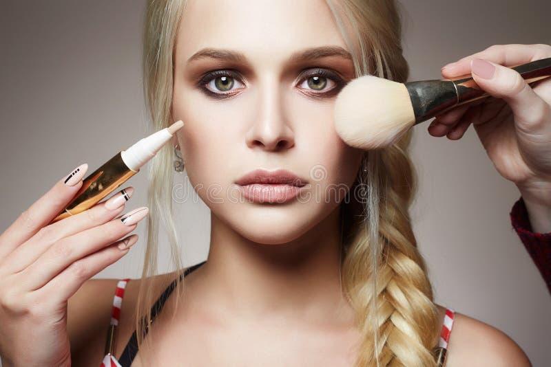 Smink applicera skönhetsmedel modellblondinflicka royaltyfri foto