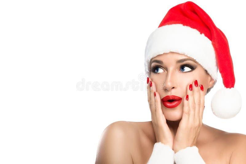 smink för skönhetjulflicka Ursnygg ung kvinna i en jultomtenhatt royaltyfria foton