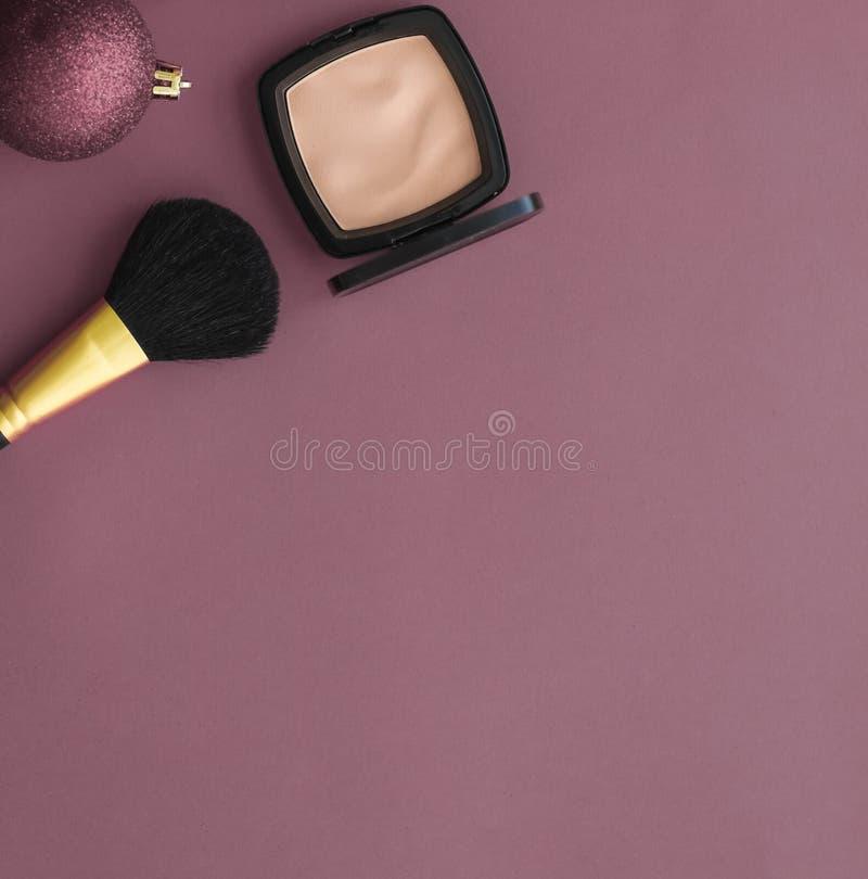 Smink- och kosmetikaprodukter som är inställda för säljfrämjande åtgärder för skönhetsmärkning under julen, en lyxlila plack bakg arkivbilder