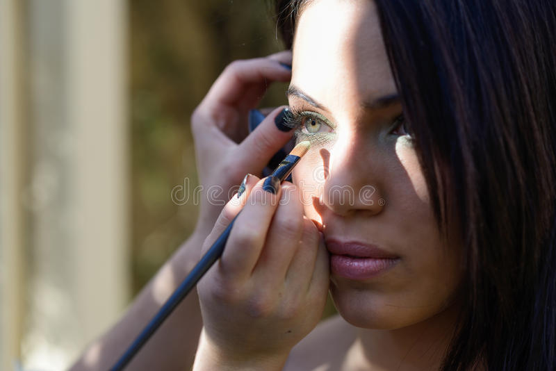 Smink som applicerar ögonskugga på modells öga arkivbild