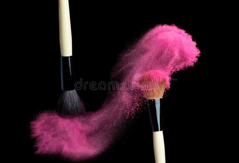Sminkborste med rosa färgpulver som isoleras på svart arkivbild